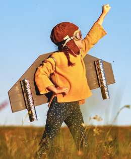 child playing in field with rocket pack